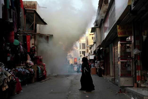 A Bahraini woman walks through market streets filled with tear gas in Manama, Bahrain, Friday. Hundreds of anti-government protesters clashed with riot police in Bahrain's capital after authorities denied a request for a major opposition rally. Photo: AP