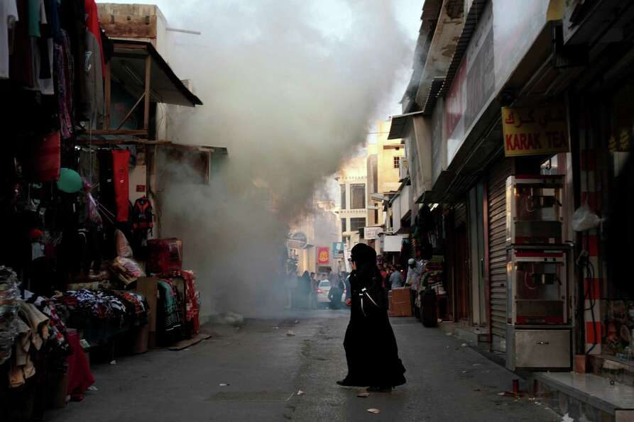 A Bahraini woman walks through market streets filled with tear gas in Manama, Bahrain, Friday. Hundr