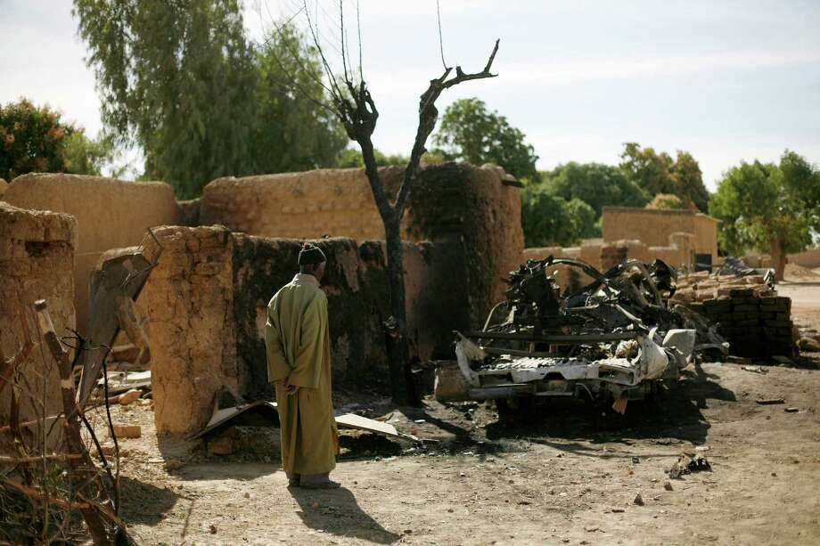 An elderley man looks at the charred  remains of  a truck used by  radical Islamists on the outskirt of Diabaly, Mali,  some 320 miles North of the capital Bamako on Monday.  French and Malian troops took control Monday of the town of Diabaly, patrolling the streets in armored personnel carriers and inspecting the charred remains of a pickup truck with a mounted machine gun left behind by the fleeing militants. Photo: AP