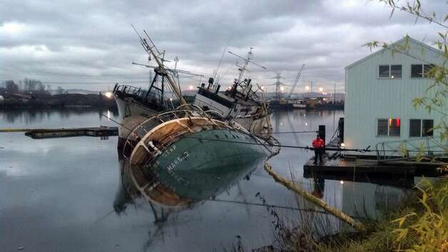 In this handout photo provided by the U.S. Coast Guard, a pair of derelicts boats are seen partially submerged and listing early Friday on the Hylebos Waterway in Tacoma, Wash. The 167-foot Helena Star, front, sank early Friday while the 130-foot Golden West, tied to the other ship, was listing. Officials say fuel was removed from the boats nearly a near ago and both were intended to be dismantled. Photo: AP