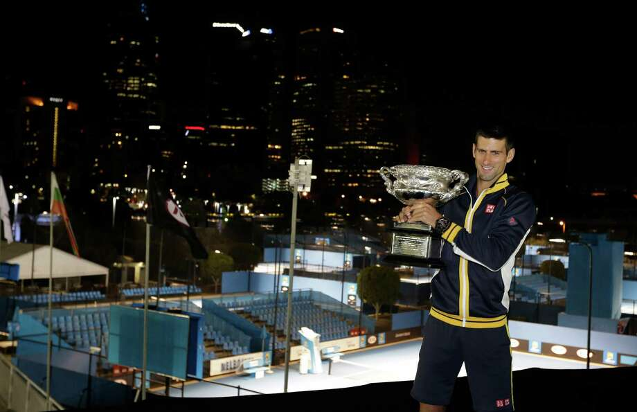 Serbia's Novak Djokovic poses for photographers as he holds his trophy aloft after defeating Britain's Andy Murray in the men's final at the Australian Open tennis championship in Melbourne, Australia, Monday, Jan. 28, 2013.  (AP Photo/Andy Wong) Photo: Andy Wong, STF / AP