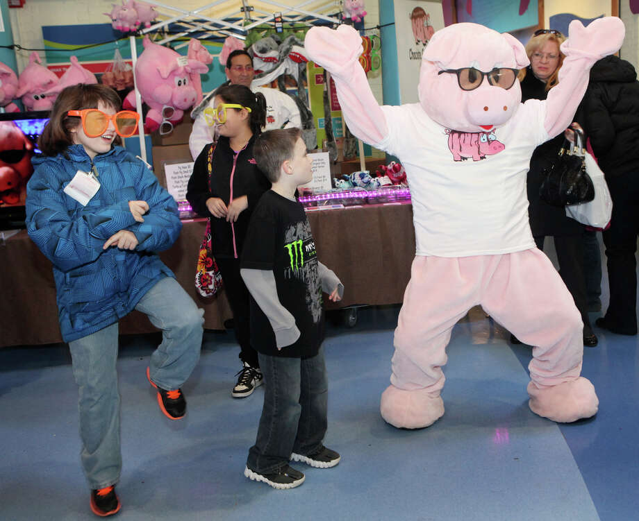 Children, from left, Andrea Albu, 11, of Bethel, Amanda Lucadamo, 10, of Bethel, and Gavin Nadeau, 8, of Wilcott, dance with a pig from Bacon Bites, of Roseland, NJ, at the Chocolate World Expo at the Maritime Aquarium in Norwalk, Conn. on Sunday, January 27, 2013. Photo: BK Angeletti, B.K. Angeletti / Connecticut Post freelance B.K. Angeletti