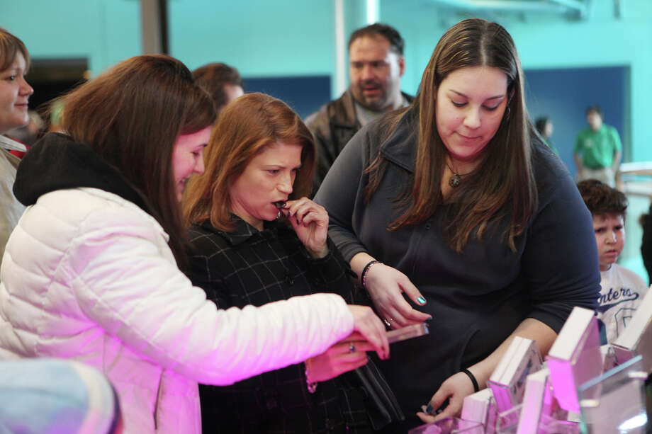 Friends, from left, Hope Pardee, of Milford, Pam Askinazi, of Norwalk, and Jennifer Paul, of Norwalk, taste chocolate covered bacon from Bacon Bites, of Roseland, NJ, at the Chocolate World Expo at the Maritime Aquarium in Norwalk, Conn. on Sunday, January 27, 2013. Photo: BK Angeletti, B.K. Angeletti / Connecticut Post freelance B.K. Angeletti