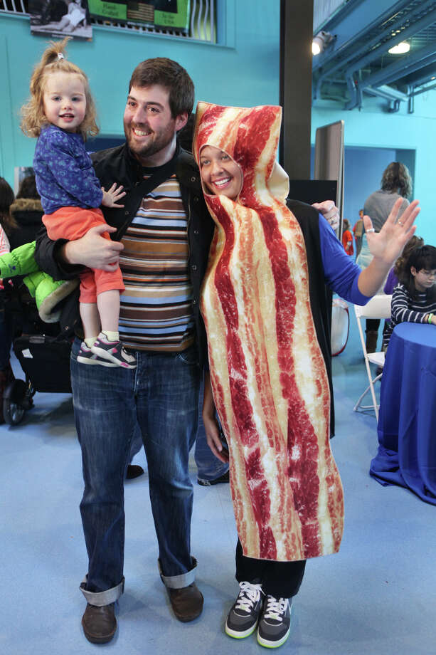 Aven Craddoch, 2, of Bridgeport, and her father, Grayson, take a picture with bacon, Sarah Dowell, at the Chocolate World Expo at the Maritime Aquarium in Norwalk, Conn. on Sunday, January 27, 2013. Photo: BK Angeletti, B.K. Angeletti / Connecticut Post freelance B.K. Angeletti