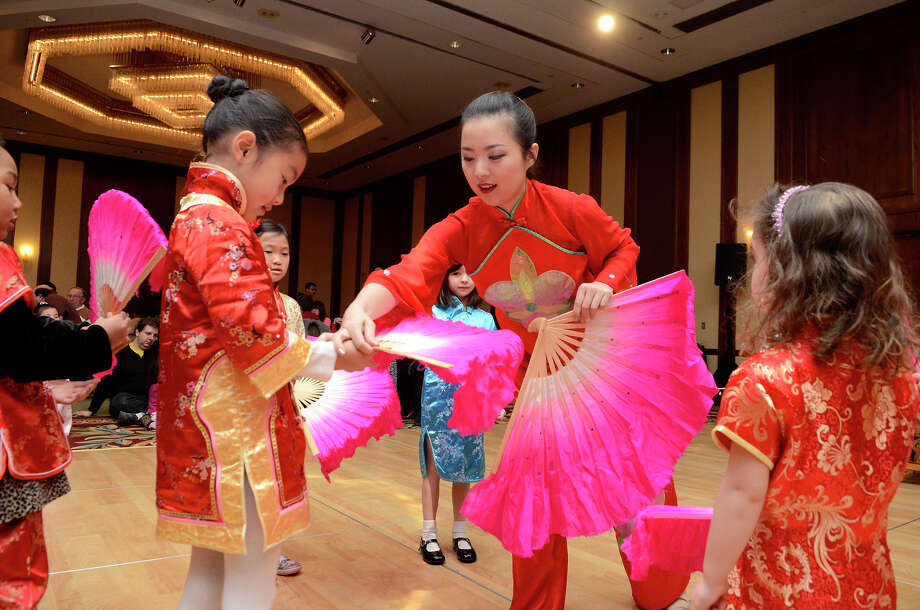 Fan dancing instructor Xu Wen, New York City, helps Sofie Fu, 6, Rye, New York, as the Chinese Language School of Connecticut hosts a Chinese New Year Celebration, recognizing The Year of the Snake, at the Hilton Stamford Hotel and Executive Meeting Center in Stamford, CT on Sun., Jan. 27, 2013. Photo: Shelley Cryan / Shelley Cryan for the Stamford Advocate/ freelance Shelley Cryan