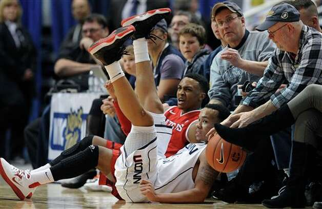 Rutgers' Myles Mack, rear, reacts as he is called for traveling after falling into fans with Connecticut's Shabazz Napier, front, during the second half of an NCAA college basketball game in Hartford, Conn., Sunday, Jan. 27, 2013. Connecticut won 66-54. (AP Photo/Jessica Hill)