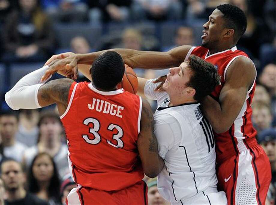 Connecticut's Tyler Olander, center, is sandwiched between Rutgers' Wally Judge, left, and Kadeem Jack, right, as they vie for a rebound during the second half of an NCAA college basketball game in Hartford, Conn., Sunday, Jan. 27, 2013. Connecticut won 66-54. (AP Photo/Jessica Hill)