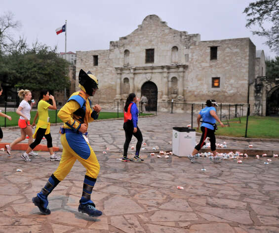 Runners wearing super hero costumes run in front of the Alamo during the inaugural  Hero-thon half-marathon Sunday morning. The event benefits the Leukemia and Lymphoma Society. Photo: Robin Jerstad