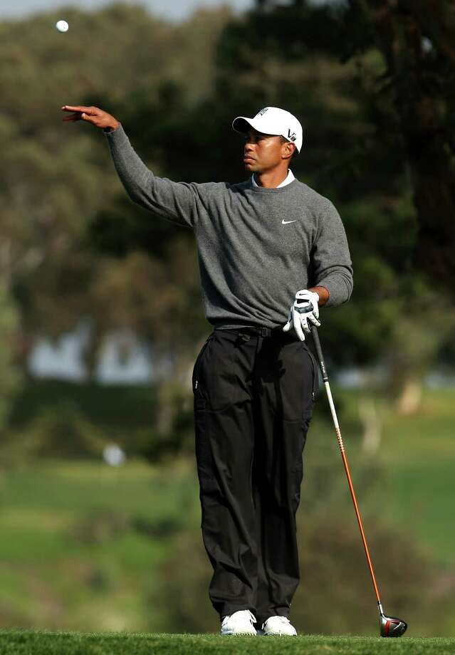 Tiger Woods tosses his ball to his caddie on the tee on the fifth hole during the third round of the Farmers Insurance Open on the South Course at Torrey Pines Golf Course on January 27, 2013 in La Jolla, California. Photo: Stephen Dunn, Getty Images / 2013 Getty Images