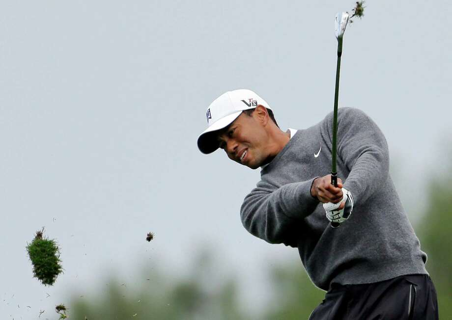 Tiger Woods sends his divot flying as he hits a pitching wedge to the second green, which stopped inches from the hole for a birdie, during the third round of the Farmers Insurance Open golf tournament on Sunday, Jan. 27, 2013, in San Diego. (AP Photo/Lenny Ignelzi) Photo: Lenny Ignelzi, Associated Press / AP