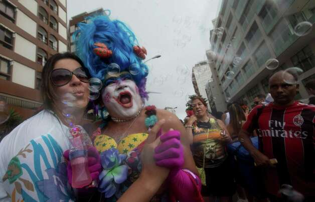 Revelers make bubbles with a bubble blowing gun during the Banda de Ipanema block parade, a pre-Carnival event, in Rio de Janeiro, Brazil, Saturday. Photo: AP