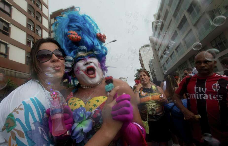Revelers make bubbles with a bubble blowing gun during the Banda de Ipanema block parade, a pre-Carn
