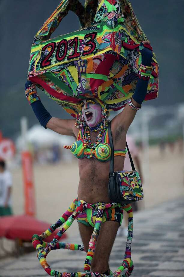 Eduardo Rasberge, 48, known as Suitcase Woman wearing a decorative suitcase on his head, topped with a replica of the Eiffel Tower, makes his way to the Banda de Ipanema block parade, a pre-Carnival event, in Rio de Janeiro, Brazil, Saturday. Rasberge said, inspired by singer Carmen Miranda, the Suitcase Woman has been a Carnival regular for the past 30 years. Photo: AP