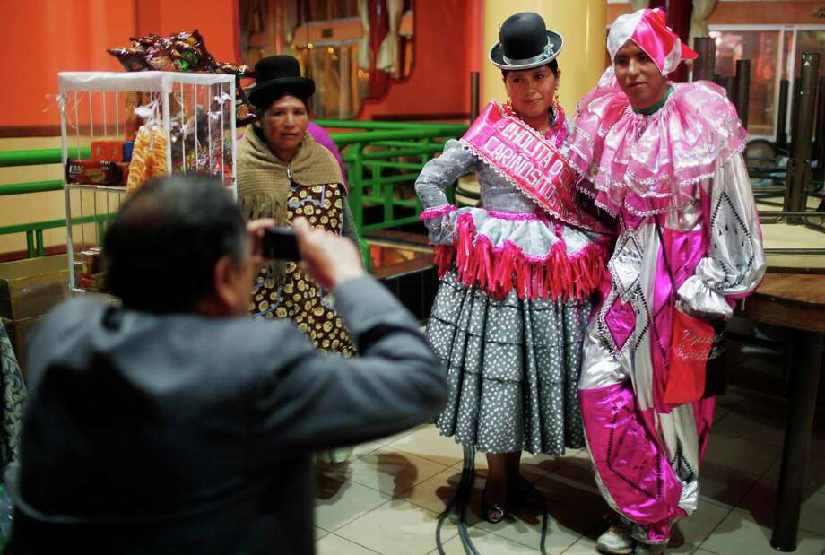 A Chola and a Pepino contestant pose for pictures before the start of a local competition to elect the three main Carnival characters, Chuta, Pepino and Chola, in La Paz, Bolivia, Friday. Photo: AP