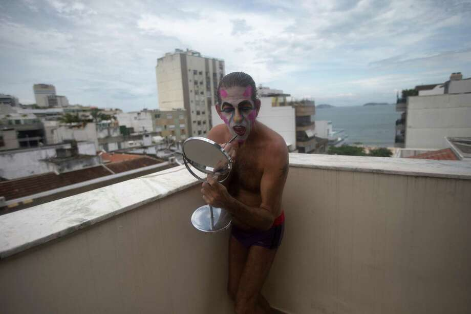 Eduardo Rasberge, 48, known as Suitcase Woman paints his lips while standing on his balcony as he prepares for the Banda de Ipanema block parade, a pre-Carnival event, in Rio de Janeiro, Brazil, Saturday.  Photo: AP