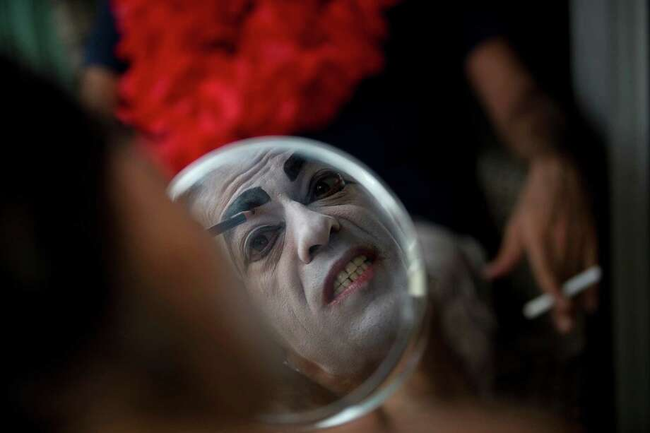 Eduardo Rasberge, 48, known as Suitcase Woman paints his face as he prepares for the Banda de Ipanema block parade, a pre-Carnival event, in Rio de Janeiro, Brazil, on Saturday.  The Suitcase Woman has been a Carnival regular for the past 30 years, honoring women and inspired by singer Carmen Miranda. Photo: AP