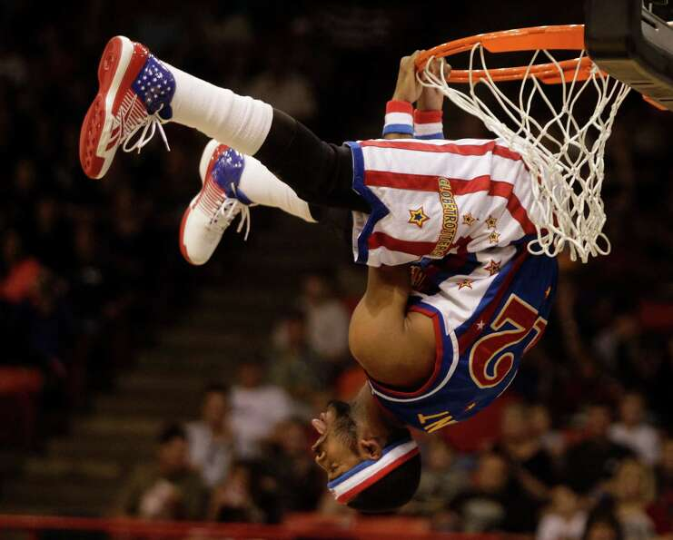 Harlem Globetrotters player Ant Atkinson hangs from the basket during a performance at Reliant Arena