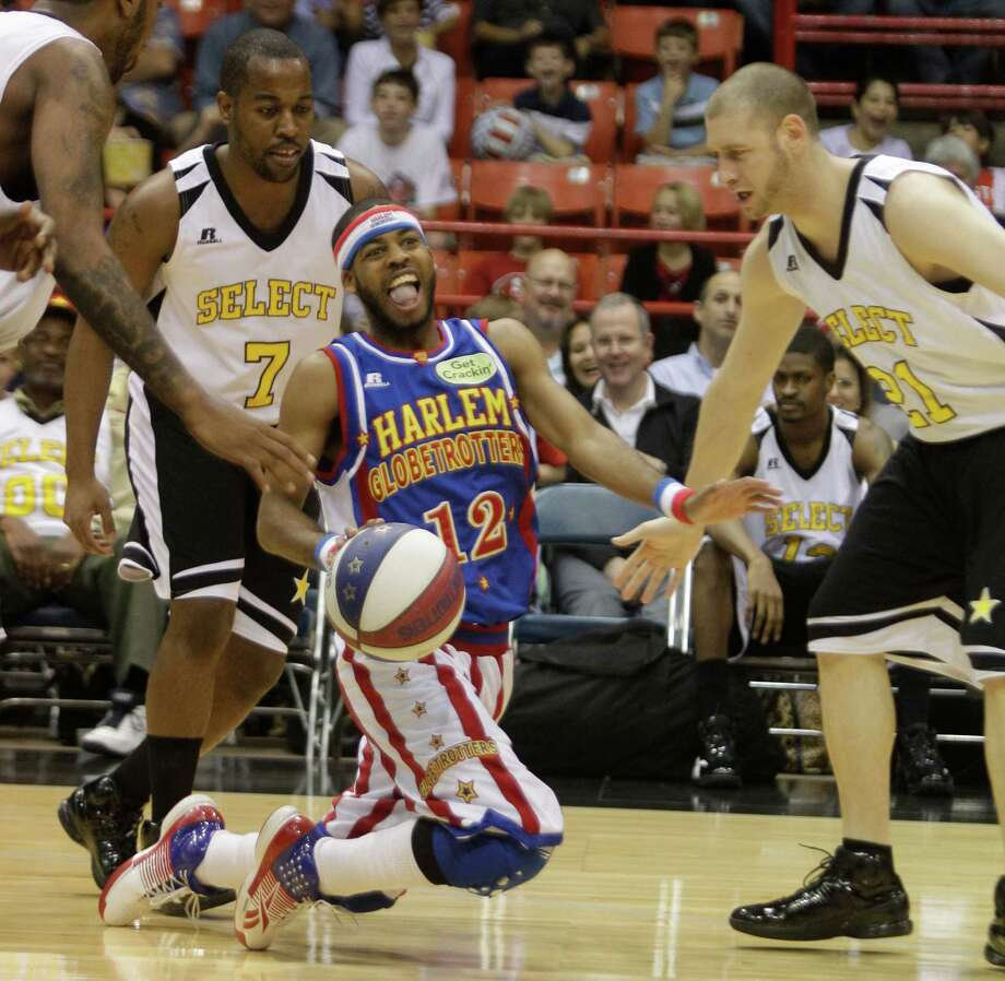 Harlem Globetrotters player Ant Atkinson keeps the ball away from the Select players during performance at Reliant Arena  Sunday, Jan. 27, 2013, in Houston. Photo: Melissa Phillip, Houston Chronicle / © 2013 Houston Chronicle