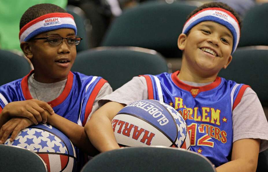 Spencer Miles, 9, left, and his brother, Alec Miles, 12, right,  watch the Harlem Globetrotters duri