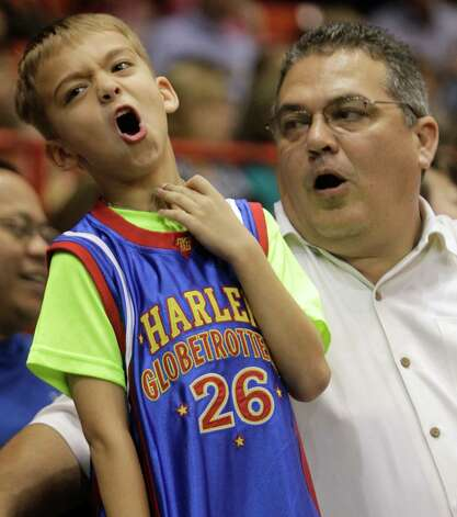 Tyler Rosson, 7, and his father, Doug Rosson, of Houston react as they watch the Harlem Globetrotters during performance at Reliant Arena  Sunday, Jan. 27, 2013, in Houston. Photo: Melissa Phillip, Houston Chronicle / © 2013 Houston Chronicle