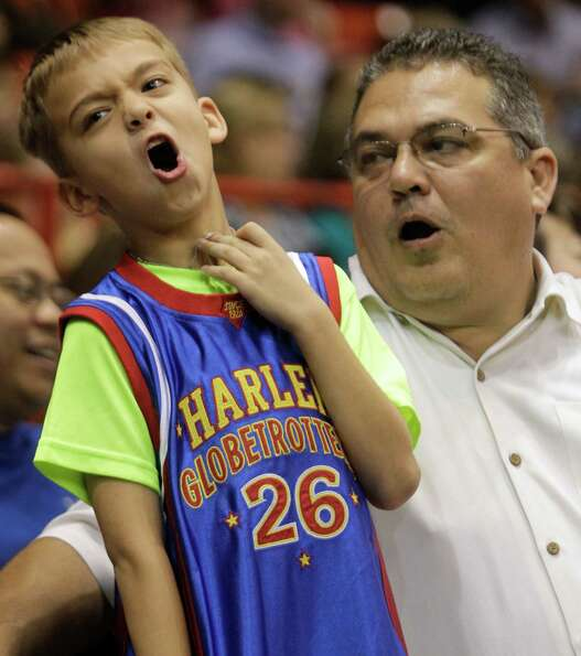 Tyler Rosson, 7, and his father, Doug Rosson, of Houston react as they watch the Harlem Globetrotter