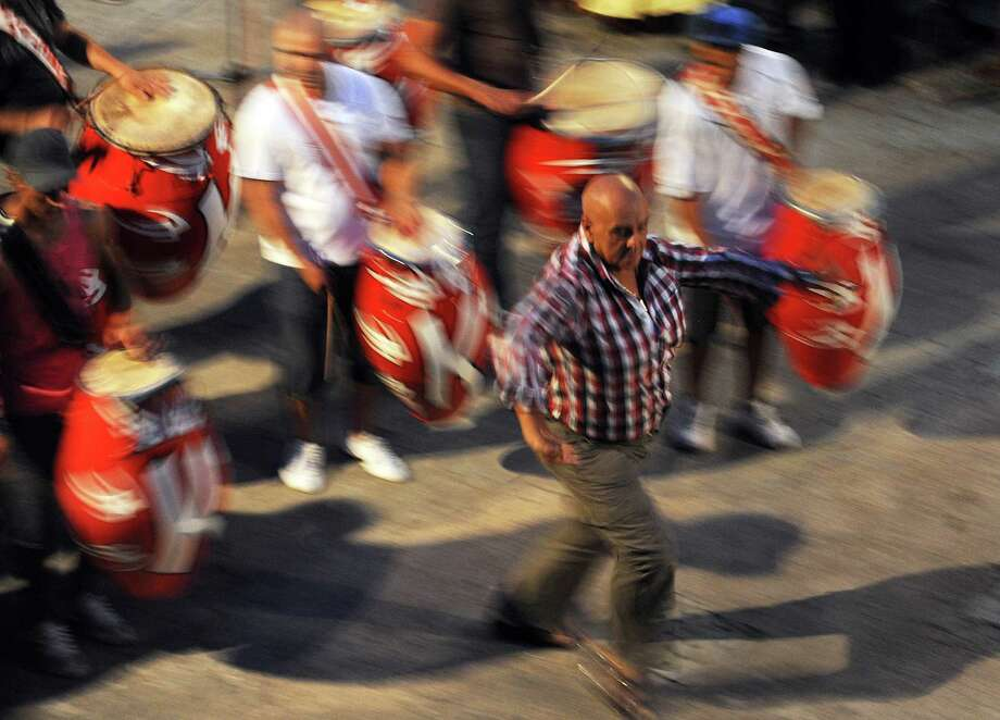 Julio Sosa(C), aka Kanela, director of one of the most important carnival groups of Uruguay, dances among drums in Montevideo on Wednesday.  Photo: MIGUEL ROJO, Getty / 2013 AFP