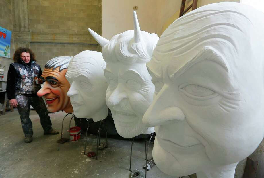 Italian artist Massimo Breschi stands by a giant carnival masks showing Italian politicians (From L) Pier Ferdinando casini, Angelino Alfano, Beppe Grillo, Pier Luigi Bersani and Niki Vendola at the Cittadella del Carnevale, the workshops where the masks and floats for the carnival of Viareggio are being built. Photo: AFP, Getty / 2013 AFP
