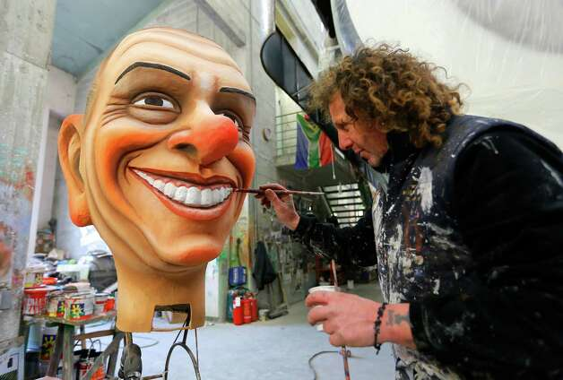 Italian artist Massimo Breschi paints a giant carnival mask showing Silvio Berlusconi at the Cittadella del Carnevale, the workshops where the masks and floats for the carnival of Viareggio are being built on Wednesday in Viareggio. The carnival of Viareggio runs from February 3 to March 3, 2013 with parades of floats and masks, depicting caricatures of popular people, such as politicians, showmen and sportsmen.  Photo: AFP, Getty / 2013 AFP