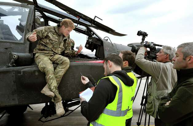 FILE - In this Dec. 12, 2012 file photo, Britain's Prince Harry talks to a TV crew after making his early morning pre-flight checks on the flight line, at Camp Bastion southern Afghanistan. During Prince Harry's 20-week deployment in Afghanistan, he served as an Apache helicopter pilot with the Army Air Corps. (AP Photo/John Stillwell, Pool, File) Photo: John Stillwell