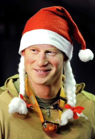 FILE - In this Dec. 12, 2012 file photo, Britain's Prince Harry wears a Santa hat as he shows a media crew his sleeping area at the VHR (very high readiness) tent, close to the flight-line, at Camp Bastion southern Afghanistan. During Prince Harry's 20-week deployment in Afghanistan, he served as an Apache helicopter pilot with the Army Air Corps. (AP Photo/ John Stillwell, Pool, File) Photo: John Stillwell