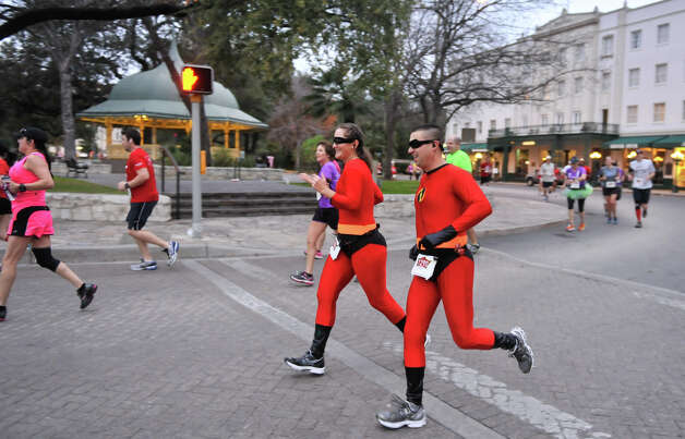 Nikki and Brian Haines dressesd as the Incredibles, run around Alamo Plaza  during the inaugural  Hero-thon half-marathon Sunday morning. The event benefits the Leukemia and Lymphoma Society. Photo: Robin Jerstad