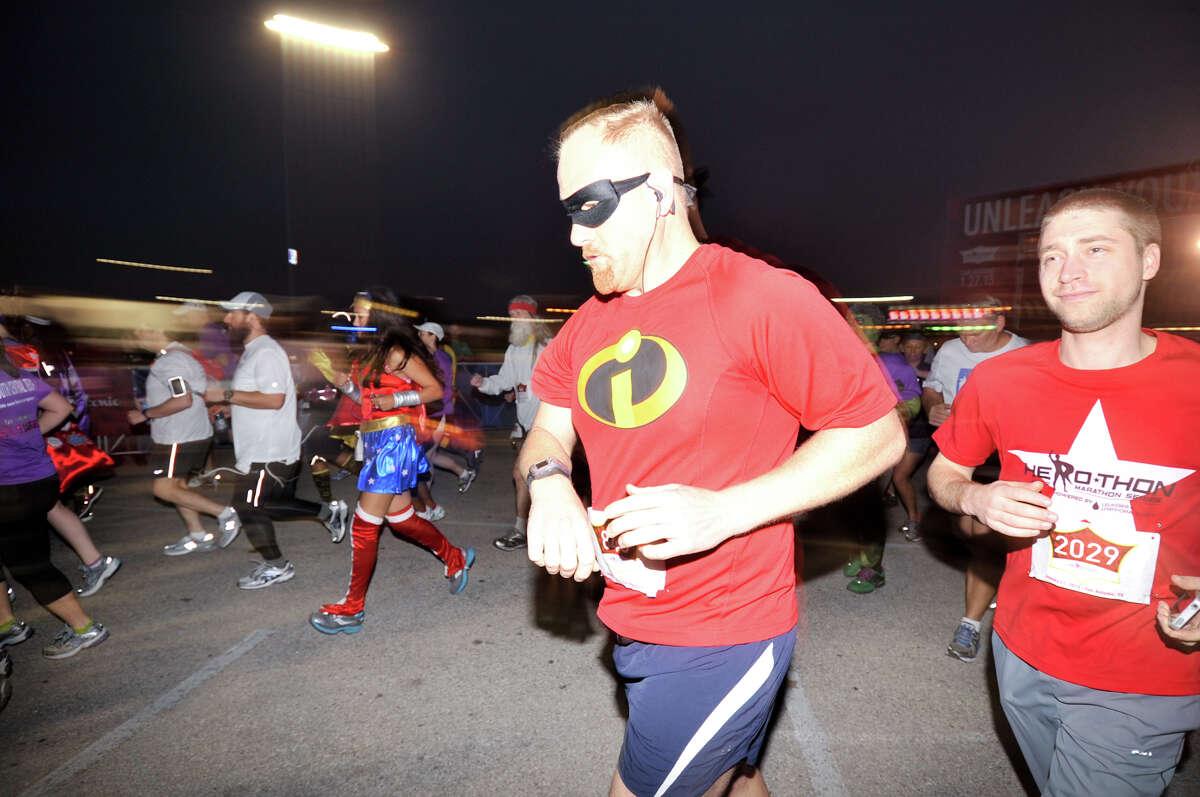 Runners wearing superhero costumes start the inaugural Hero-thon half-marathon early Sunday at the Alamodome. The event benefits the Leukemia and Lymphoma Society.