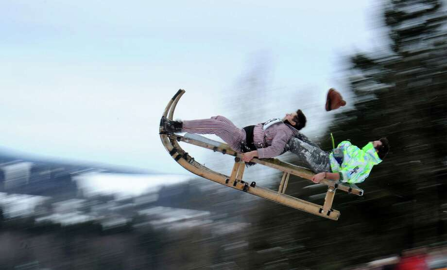 Two men ride their  sled during the traditional Schnablerrennen sled race in Gaissach, Germany, on Sunday. Over 100 costumed sled racers took part in the traditional event. The race is held annually on sleighs used formerly to bring down hay or logs from the mountains.  (AP Photo/dpa/Tobias Hase) Photo: Multiple