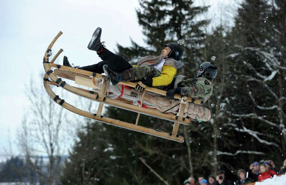 Two men ride their  sled during the traditional Schnablerrennen sled race in Gaissach, Germany, Sunday.  (AP Photo/dpa/Tobias Hase) Photo: Multiple