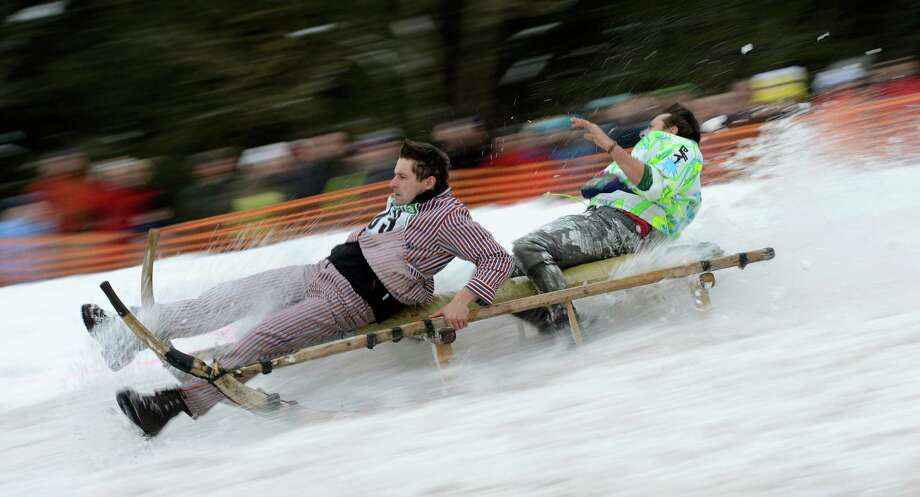 Participants race with their sled during the traditional Schnablerrennen sledge race. (CHRISTOF STACHE/AFP/Getty Images) Photo: CHRISTOF STACHE, Multiple / 2013 AFP