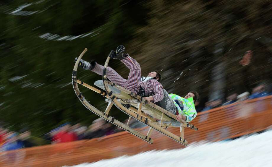 Participants jump with their sled during the traditional Schnablerrennen sledge race. (CHRISTOF STACHE/AFP/Getty Images) Photo: CHRISTOF STACHE, Multiple / 2013 AFP