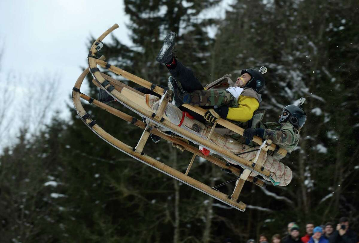 Participants jump with their sled during the traditional Schnablerrennen sledge race in a valley near the Bavarian village Gaissach, southern Germany, on Sunday. (CHRISTOF STACHE/AFP/Getty Images)