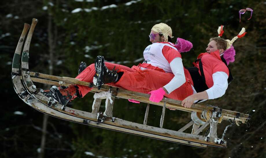 Participants jump with their sled during the traditional Schnablerrennen sledge race in a valley near the Bavarian village Gaissach, southern Germany, on Sunday. (CHRISTOF STACHE/AFP/Getty Images) Photo: CHRISTOF STACHE, Multiple / 2013 AFP