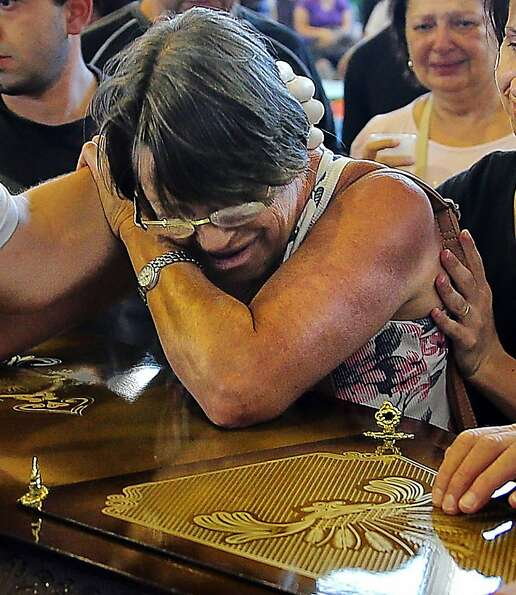 Relatives of victims from a fire that broke out at a nightclub weep during their funeral in Santa Ma