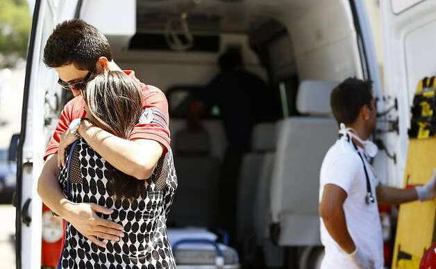Relatives of victims embrace next to an ambulance after a fire at a nightclub in Santa Maria, 550 Km from Porto Alegre, southern Brazil on January 27, 2012. The death toll from a fire that tore through a Brazilian nightclub packed with students has risen to 245, an official said Sunday as investigators dug through the charred remains of the building. AFP PHOTO / AGENCIA RBS /Felix Zucco / BRAZIL OUTFelix Zucco/AFP/Getty Images Photo: Felix Zucco, AFP/Getty Images