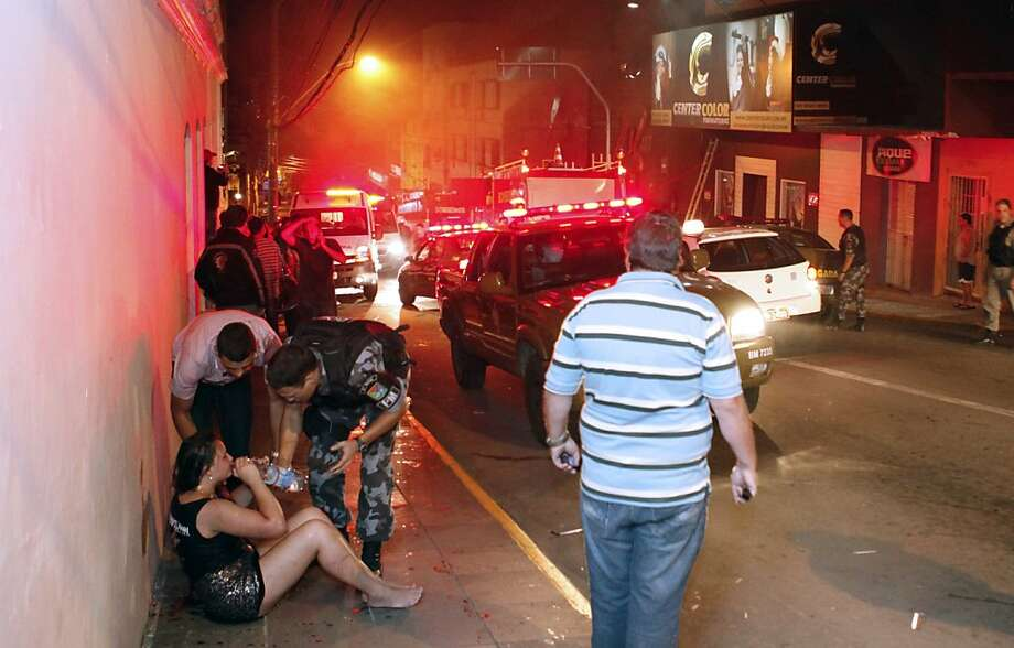 Police agents give water to a woman after a fire at a nightclub in Santa Maria, 550 Km from Porto Alegre, southern Brazil on January 27, 2012. More than 150 people died early Sunday when a fire tore through a nightclub in the southern Brazilian city of Santa Maria during a boisterous student party, police said. Brazilian President Dilma Rousseff interrupted her visit to Chile. AFP PHOTO / AGENCIA RBS / LAURO ALVES / BRAZIL OUTLAURO ALVES/AFP/Getty Images Photo: Lauro Alves, AFP/Getty Images