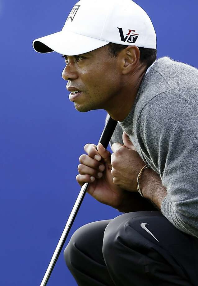 Tiger Woods, surveying a third-round putt, was at 17-under after seven holes of the fourth. Photo: Gregory Bull, Associated Press