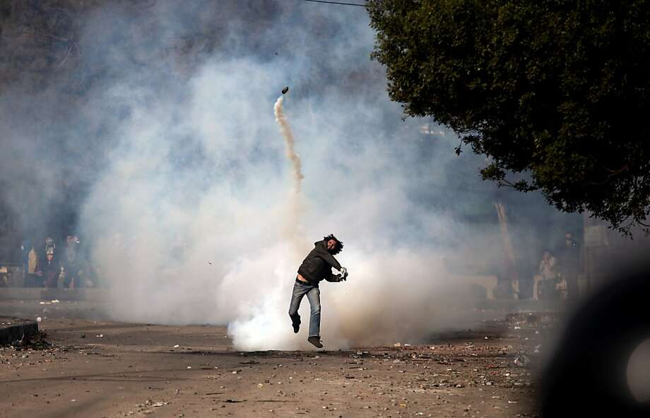 An Egyptian protester throws a tear gas canister back at riot police, not seen, during clashes near Tahrir Square, Cairo, Egypt, Sunday, Jan. 27, 2013. Clashes continued for the fourth successive day between protesters and police near Cairo's central Tahrir square, birthplace of the 2011 uprising. Police used tear gas, while the protesters pelted them with rocks. Photo: Khalil Hamra, Associated Press