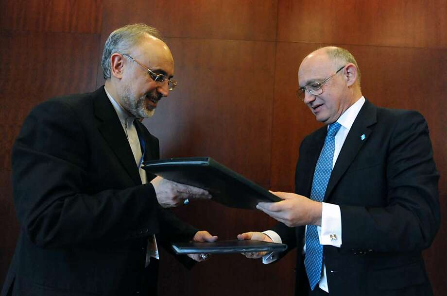 Handout picture released by the Argentinian Presidency of Argentinian Minister of Foreign Affairs Hector Timerman (R) and his Iranian counterpart Ali Akbar Salehi as they exchange documents in Addis Ababa, Ethiopia on January 27, 2013, after signing an agreement memorandum on the 1994 attacks to the Argentine Israelite Mutual Association (AMIA) in Buenos Aires. The signing took place in the framework of the African Union biannual summit. AFP PHOTO / ARGENTINIAN PRESIDENCYHO/AFP/Getty Images Photo: Ho, AFP/Getty Images