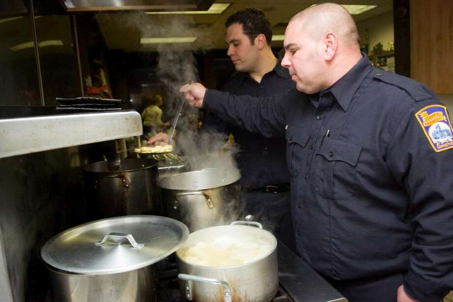 Firefighters Fabio Basile, right, and Nick Tamburro, left, prepare a tortellini chicken soup for Christmas dinner at the Central Fire Headquarters (Station 1) in Stamford, Conn. on Christmas day, Friday, Dec. 25, 2009. Photo: Chris Preovolos / Stamford Advocate