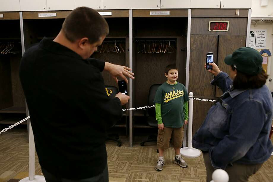 Kurt Jourdan (left), of West Sacramento, and his wife Christy (right) take photos of their son Hal,11, in front of the locker Oakland Athletics outfielder Yoenis Cspedes at the A's Fanfest at the Oracle Arena on Sunday, January 27, 2013 in Oakland, Calif. Photo: Beck Diefenbach, Special To The Chronicle