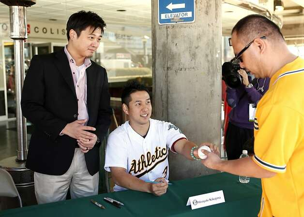 Interpreter Hiroo Nishi (left) assists as new Oakland Athletics shortstop Hiroyuki Nakajima signs an autograph for a fan at the A's Fanfest at the Oracle Arena on Sunday, January 27, 2013 in Oakland, Calif. Photo: Beck Diefenbach, Special To The Chronicle