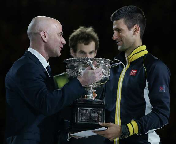 Serbia's Novak Djokovic, right, is presented with the trophy by former Australian Open champion Andre Agassi after defeating Britain's Andy Murray, center, in the men's final at the Australian Open tennis championship in Melbourne, Australia, Sunday, Jan. 27, 2013. (AP Photo/Aaron Favila) Photo: Aaron Favila