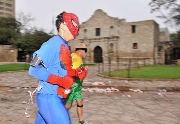 Runners wearing superhero costumes run in front of the Alamo during the inaugural  Hero-thon half-marathon Sunday morning. The event benefits the Leukemia and Lymphoma Society. Photo: Robin Jerstad