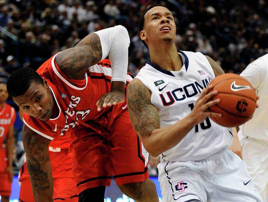 Connecticut's Shabazz Napier, right, drives to the basket while Rutgers' Wally Judge, left, defends during the second half of an NCAA college basketball game in Hartford, Conn., Sunday, Jan. 27, 2013. Napier had 19 points for Connecticut in their 66-54 win over Rutgers. (AP Photo/Jessica Hill) Photo: Jessica Hill, Associated Press / FR125654 AP